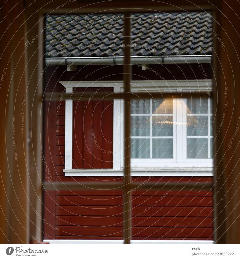 Hinter den Fenstern Haus Hütte Holzhaus Holzhütte Fischerhütte zweiundfünfzig Brett Fensterscheibe Reflexion & Spiegelung Fassade rot Lampe leuchten
