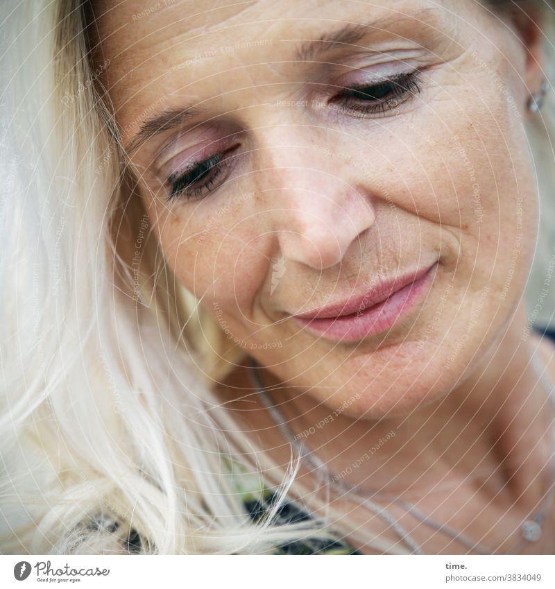 Fadila blick nach unten portrait feminin frau blond warm lächeln
