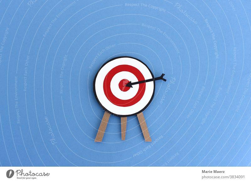 Mitten ins Ziel / Zielscheibe mit schwarzem Pfeil der in der Mitte steckt treffen Treffer perfekt Genauigkeit Erfolg Business Konzept Sport zielen