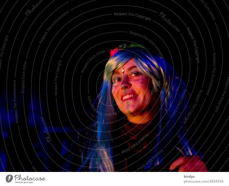 junge Frau mit bemaltem Gesicht und bunten , langen Haaren. Portrait. Zweiflerisch lächelnd attraktiv Lifestyle Blick in die Kamera Lächeln Nachtaufnahme