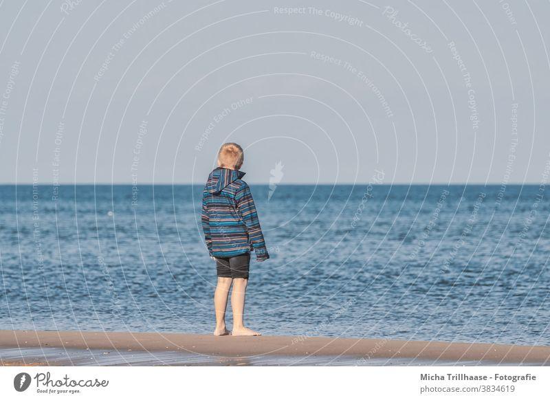 Junge blickt auf das Meer Ostsee Strand Wasser Wellen Kind blond Haare Jacke Jeanshose aufgekrempelt barfuß Sand Blick blicken schauen träumen Horizont Himmel