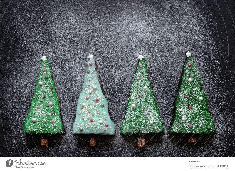 Erst eins, dann zwei, dann drei, dann vier Stück Kuchen als Tannenbäume mit grünem Zuckerguss verziert liegen auf dunkler Schieferplatte mit Puderzucker