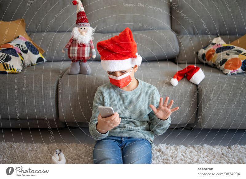 Kleiner Junge macht zu Weihnachten einen Videoanruf allein Anruf Feier Talkrunde Kind Kindheit Computer Konzept Korona Coronavirus COVID COVID19 Gerät