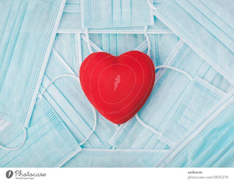 Rotes Herz auf einem Haufen medizinischer Gesichtsmasken. Konzept von Covid 19 Coronavirus Chirurgische Schutzmaske medizinische Gesichtsmasken Virus