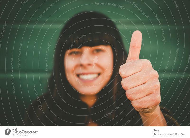 Gut gelaunte lächelnde Frau zeigt Daumen hoch in die Kamera positiv gut gelaunt Erfolg Optimismus lachen Freude Fröhlichkeit Zufriedenheit Lebensfreude grün