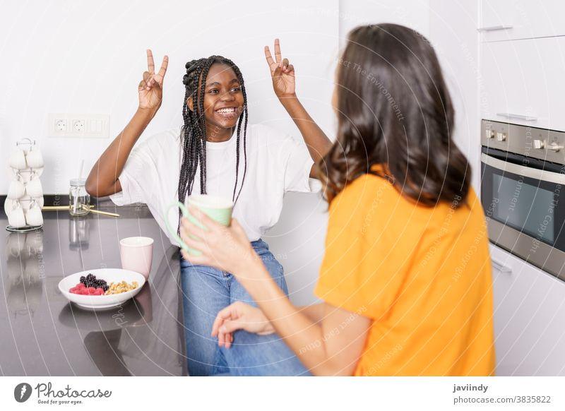 Zwei Freunde essen einen gesunden Snack, während sie sich zu Hause unterhalten Frauen Lebensmittel heimwärts Essen multiethnisch rassenübergreifend Gesundheit