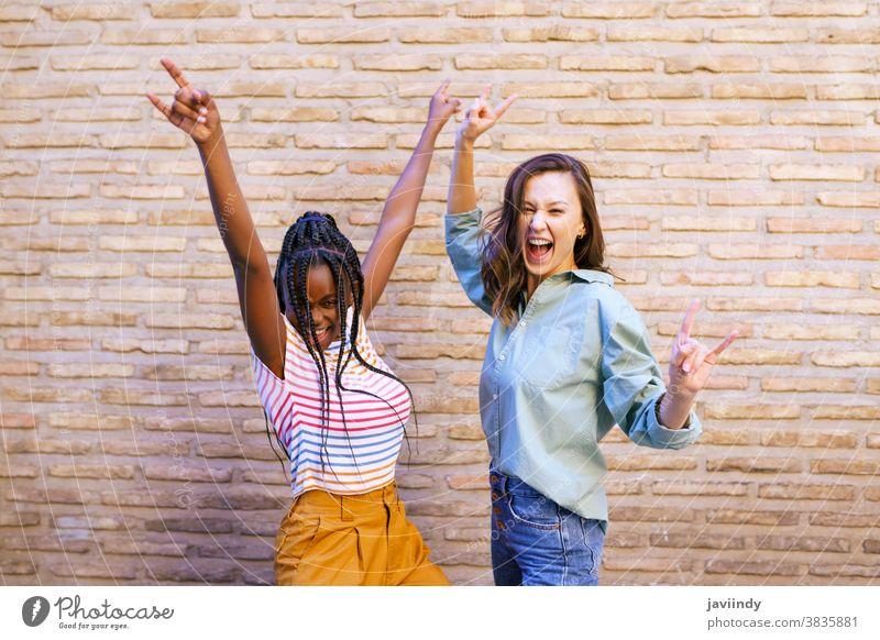 Zwei Freundinnen amüsieren sich gemeinsam auf der Straße. Multiethnische Freunde. Frauen multiethnisch Zeichen Hupe Zopf Frisur Behaarung schwarz Afro-Look
