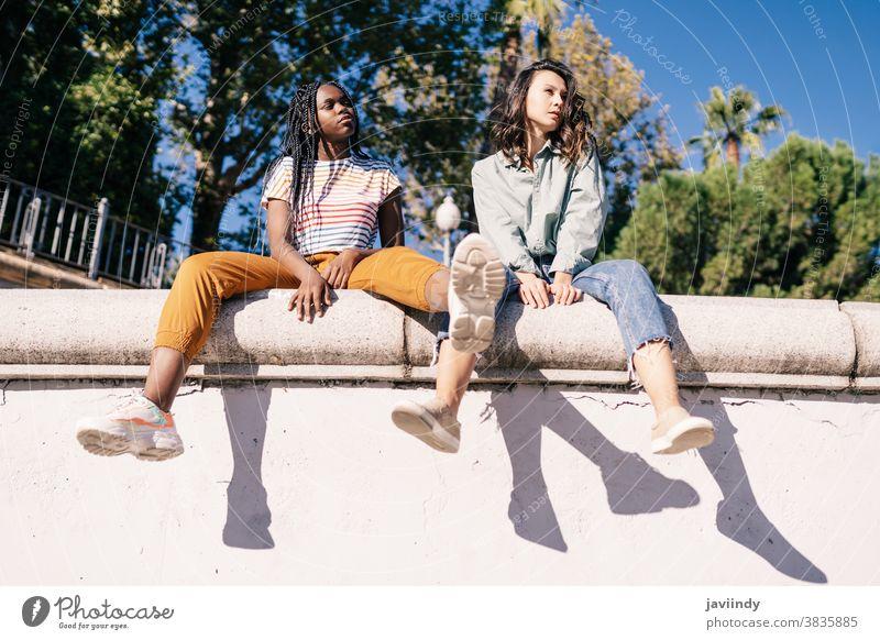 Zwei multiethnische Frauen sitzen auf einer Stadtmauer. ernst Ausdruck Sonnenlicht Freund schwarz Afro-Look Mädchen Schüler zwei Menschen Lifestyle hübsch jung