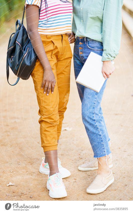 Zwei nicht erkennbare multiethnische Mädchen posieren zusammen mit farbenfroher Freizeitkleidung Frau Freund unkenntlich Tablette digital jung Lifestyle urban