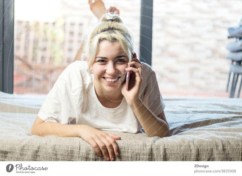 Nahaufnahme-Porträt einer süßen, attraktiven, charmanten, reizenden, liebenswerten, atemberaubenden, fröhlichen, blonden Dame, die auf dem Bett liegt und mit ihrem Freund oder Ehemann in einem hellen, weißen Innenraum plaudert