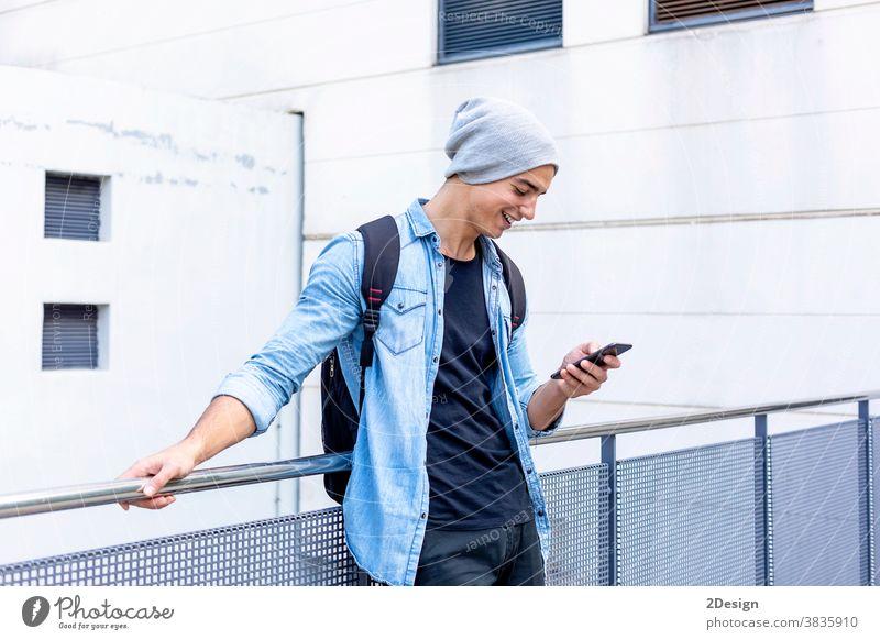 Städtischer stilvoller junger Mann, der mit seinem Handy an der Wand steht Stehen Telefon Smartphone sprechend Aufruf Typ Mobile männlich Technik & Technologie