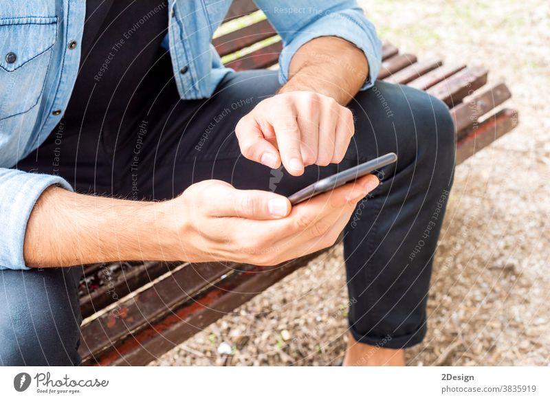 Nahaufnahme eines attraktiven jungen Mannes, der draußen auf einer Bank sitzt und sein Mobiltelefon im Freien benutzt Sitzen Beteiligung Handy Lächeln urban