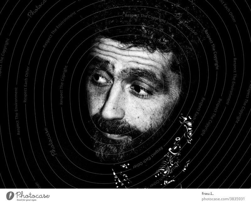 Ein skeptischer Mann Locken Bart Halstuch jung Porträt Außenaufnahme attraktiv gutaussehend sitzen nachdenklich ernst