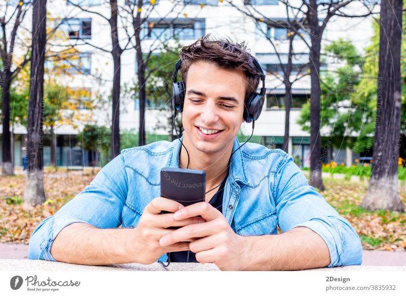 Junger Mann sieht Smartphone mit Kopfhörer auf dem Kopf Sitzen Glück hören Lächeln jung Mobile Typ Technik & Technologie Person Musik Handy benutzend urban