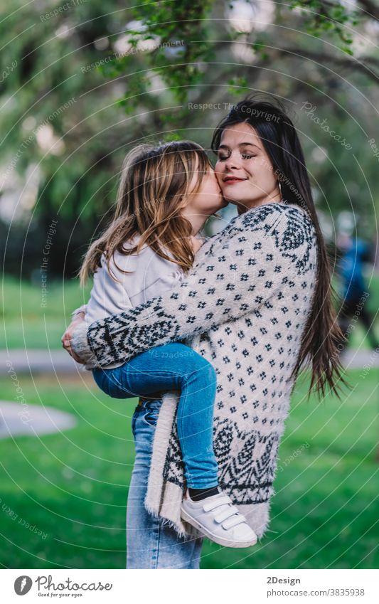 Kleines süßes Kind Baby-Mädchen küsst sich auf die Wange und umarmt, umarmt mit glücklicher hübscher Frau im grünen Park. Mutter, kleines Kind Tochter. Muttertag, Liebe Familie, Elternschaft, Kindheit