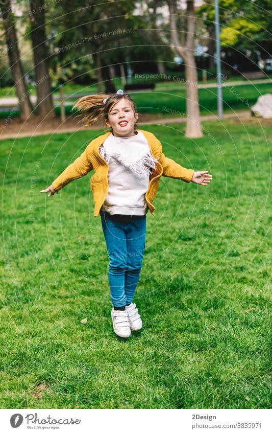 Hübsches kleines Mädchen springt an einem sonnigen Tag im Park über das Seil wenig springend im Freien 1 Glück Kindheit Fröhlichkeit spielen niedlich Spaß
