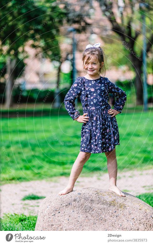 Porträt eines hübschen lächelnden kleinen Mädchens, das im Park im Freien steht. jung Lächeln bezaubernd Stehen Kind Kindheit heiter Person Kleinkind niedlich