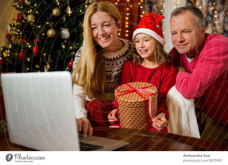 Ein glückliches Paar mit einem Kind feiert Weihnachten mit seinen Freunden per Videoanruf per Webcam. Die Familie begrüßt ihre Verwandten am Heiligabend online. Neu normal