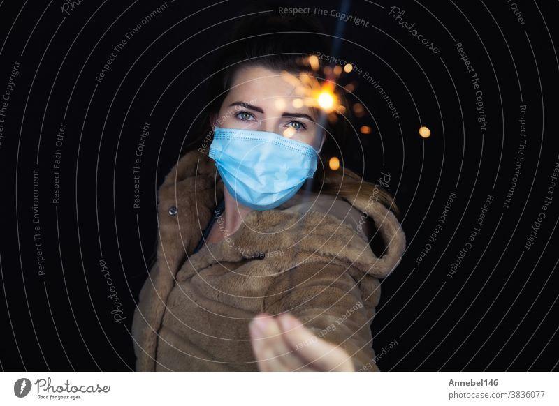 Frohes neues Jahr, Porträt einer jungen Frau, die eine medizinische Maske trägt und für Covid-19, Coronavirus und das Neujahrskonzept Wunderkerzen Licht im Dunkeln hält
