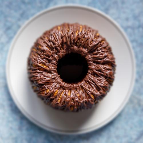 Kuchen auf Teller mit Schokoglasur in der Draufsicht, schwache Schärfentiefe von oben backen Lebensmittel Küche selbstgemacht süß frisch blau braun Auge Iris