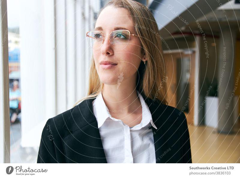 Porträt einer jungen Geschäftsfrau mit Brille, die während einer Gesundheitspandemie in einem modernen Büro steht Business arbeiten positiv selbstbewusst