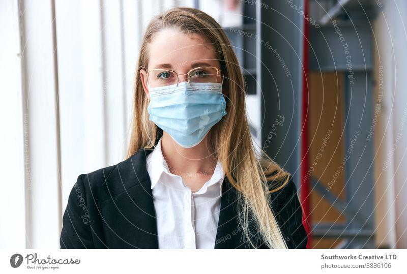 Porträt einer jungen Geschäftsfrau mit Maske, die während einer Gesundheitspandemie in einem modernen Büro steht Business Gesichtsmaske Gesichtsbedeckung