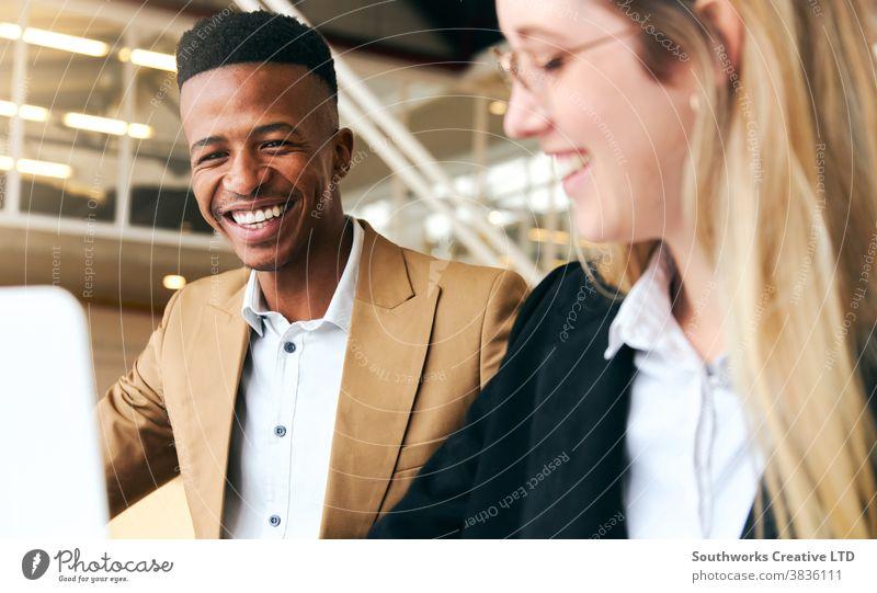 Junger Geschäftsmann und junge Geschäftsfrau treffen sich und arbeiten am Laptop am heißen Schreibtisch im modernen Büro Business Sitzung Hot Desk hotdesking