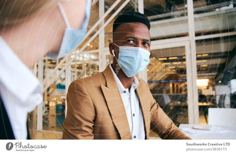 Masken tragendes Geschäftspaar trifft sich am heißen Schreibtisch im modernen Büro während einer Gesundheitspandemie Business Geschäftsmann Geschäftsfrau