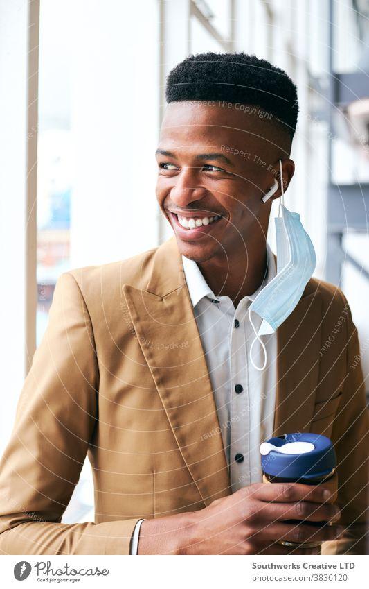 Porträt eines jungen Geschäftsmannes mit Maske, der während einer Pandemie in einem modernen Büro steht und Kaffee hält Business Gesichtsmaske Gesichtsbedeckung