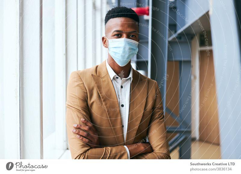 Porträt eines jungen Geschäftsmannes mit Maske, der während einer Gesundheitspandemie in einem modernen Büro steht Business Gesichtsmaske Gesichtsbedeckung