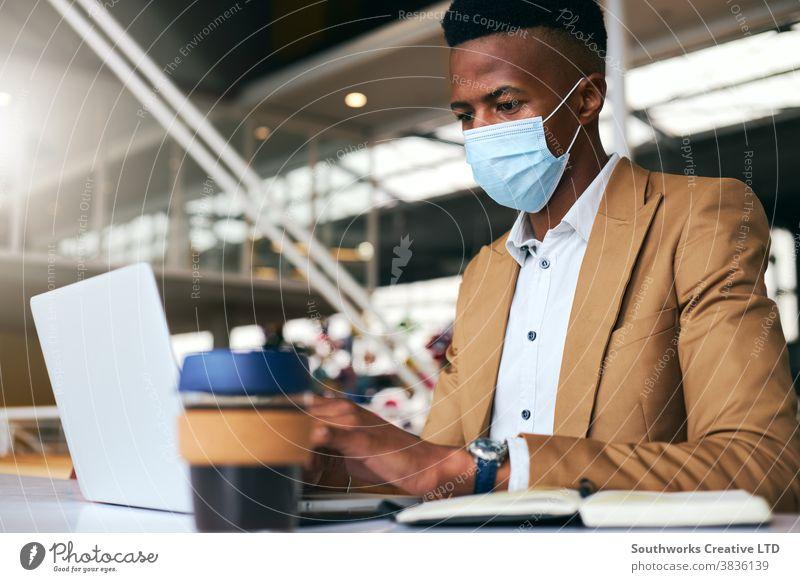 Junger Geschäftsmann mit Maske, der während einer Gesundheitspandemie am Laptop am heißen Schreibtisch im Büro arbeitet Business Gesichtsmaske Gesichtsbedeckung