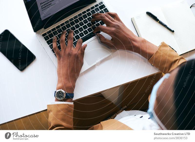 Überkopfaufnahme eines Geschäftsmannes mit Maske bei der Arbeit am Laptop am heißen Schreibtisch im Büro bei einer Gesundheitspandemie Business Gesichtsmaske