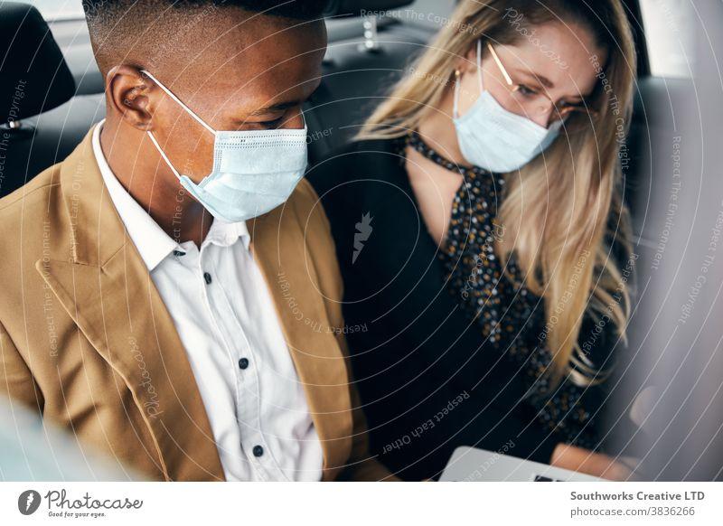 Geschäftsleute mit Masken, die während einer Gesundheitspandemie auf dem Rücksitz eines Taxis am Laptop arbeiten Business Geschäftsmann Geschäftsfrau