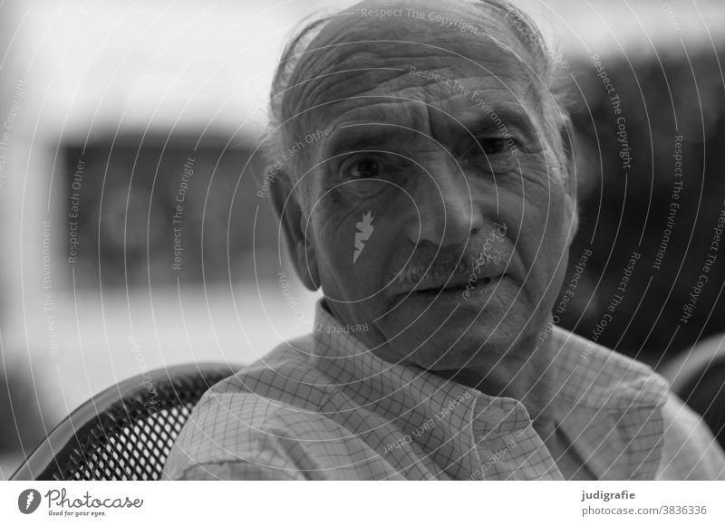 Senior blickt fragend in die Kamera. Mann Männlicher Senior Mensch 60 und älter maskulin Außenaufnahme Porträt Blick Blick in die Kamera authentisch Kopf