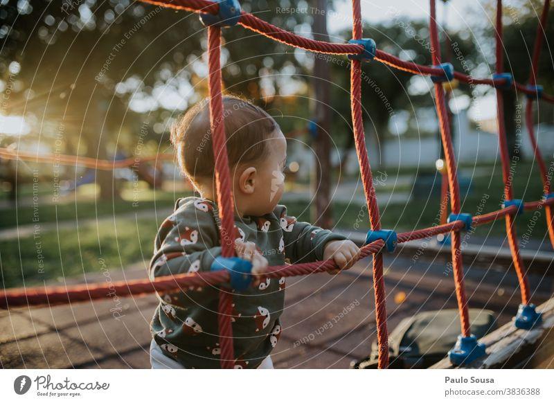 Kleinkind spielt auf dem Spielplatz Kaukasier 0-12 Monate Farbfoto eine Person Baby Mensch Tag klein niedlich Kindheit schön Glück Spielen Park Außenaufnahme