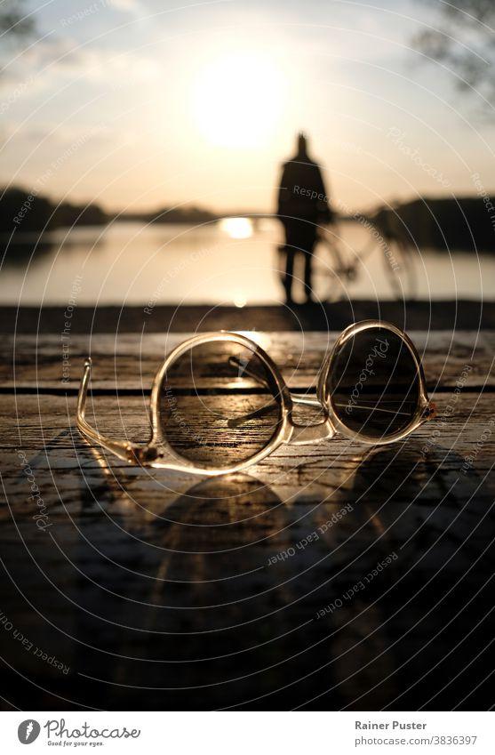 Ein ruhiger Sonnenuntergang an einem See mit einer Sonnenbrille im Vordergrund Hintergrund Windstille Ruhe Nahaufnahme Morgendämmerung Design Abenddämmerung