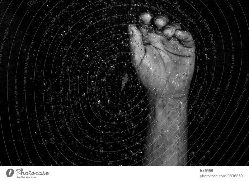 Nahaufnahme einer erhobenen Hand umgeben von Wassertropfen erhobene Hand erhobene Hände Regentropfen abstimmen kraftlos protestieren Frustration Tropen