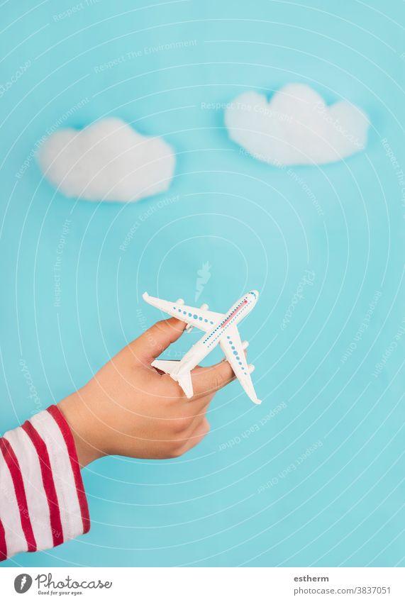 Kinderhände, die ein Spielzeugflugzeug über Wolken halten. Reise-Konzept Reisen erkunden Flieger Reisebüro Reisekonzept blau Ausflugsziel Reisender Lifestyle
