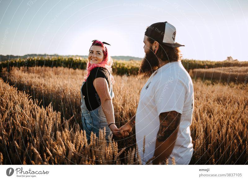 Paar mit Tattoos und pinken Haaren im Kornfeld Frau Mann Hipster trendy kuscheln innig pinke haare kornfeld Draussen paar liebe verliebt jugendlich nähe