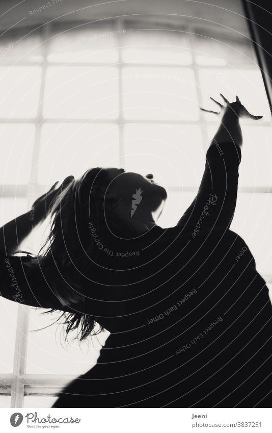 Junge Frau steht am Fenster im Gegenlicht und streckt die Arme nach oben junge Frau hoch Hände feminin Licht Sonne Silhouette Sonnenlicht Umriss Umrisslinie