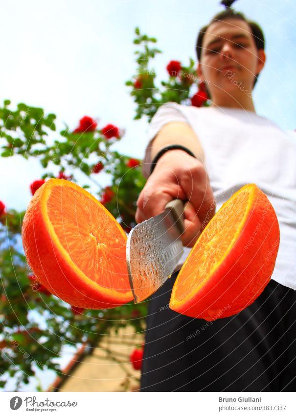 Ein Mann und eine Orange, von einem Küchenmesser in zwei Hälften geschnitten. Eine Frucht voller Vitamine. Vegetarisches oder veganes Essen. Absichtlich verschwommener Hintergrund.
