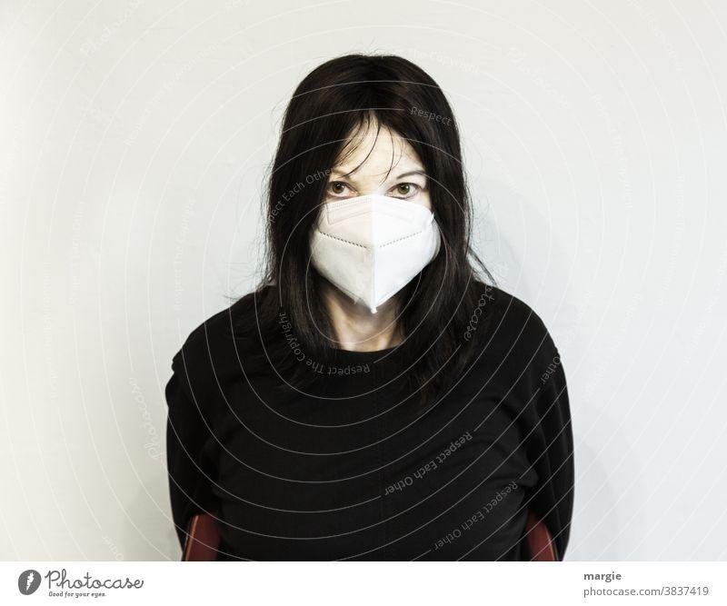 Eine verschreckte und verängstige Frau mit Mundschutz, Maske Junge Frau Maskenpflicht corona corona-krise Corona Virus schwarz schwarzhaarig verängstigt Angst