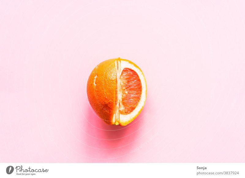 Eine aufgeschnittene Grapefruit auf einem rosa Hintergrund. roh Zitrusfrüchte Ernährung Farbfoto Gesunde Ernährung Bioprodukte Vegetarische Ernährung Gesundheit