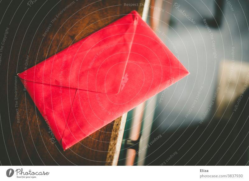 Ein verschlossener roter Briefumschlag auf einer Kommode Post Nachricht Liebesbrief dunkel schreiben