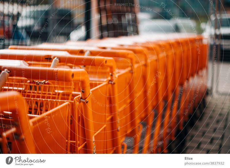 Eine Reihe orangener Einkaufswägen Baumarkt Einzelhandel einkaufen Supermarkt Einkaufswagen Handel