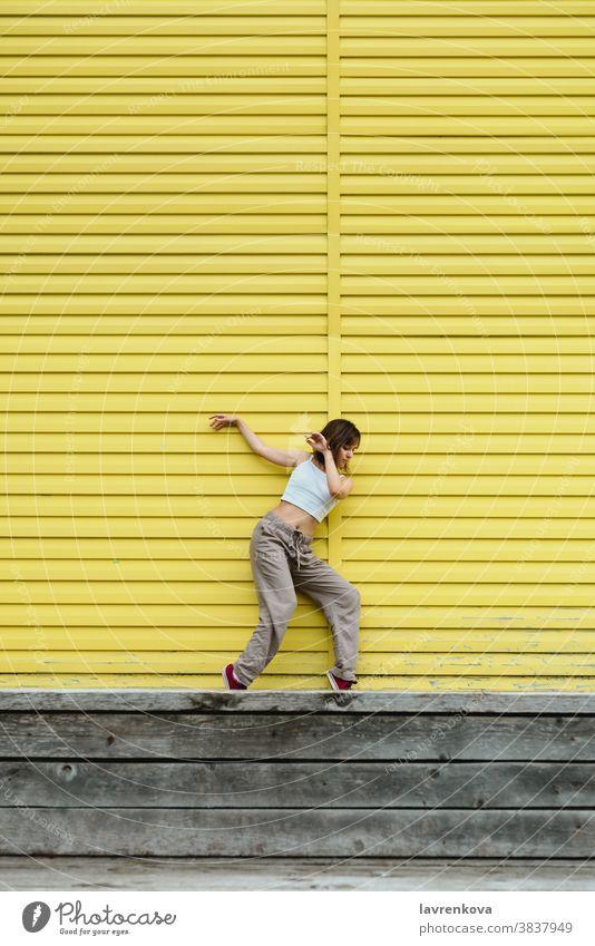 Junge erwachsene Frau in weißem Top und grauer Hose tanzt vor leuchtend gelber Wand Tänzer Choreograph hiphop im Freien Mädchen stylisch urban Bewegung Sport