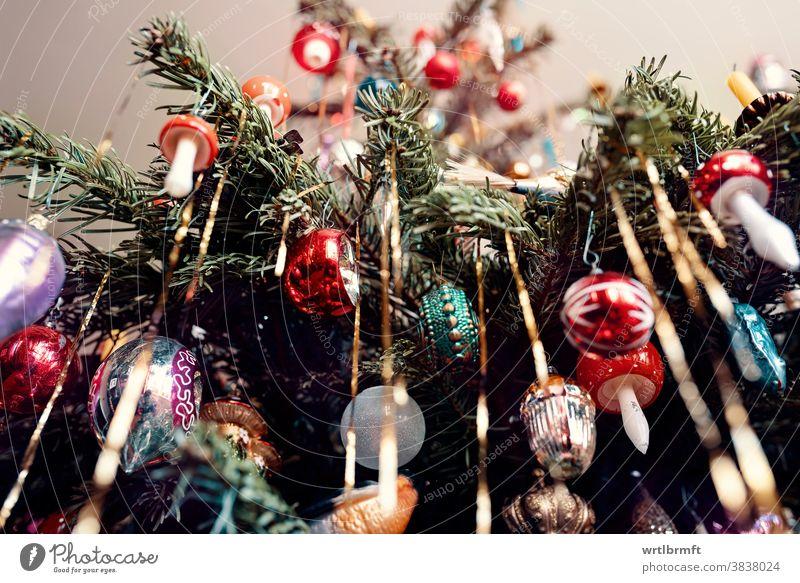 Ein Detail eines klassischen deutschen Weihnachtsbaums mit echten Kerzen und viel Lametta mit einer Vielzahl von Christbaumschmuck. Weihnachten Ornament