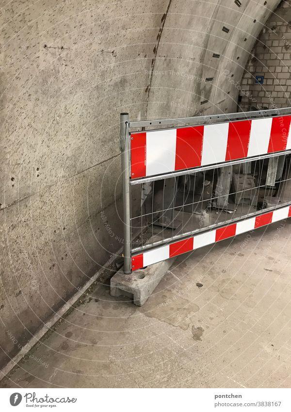 Ein rot-weiß gestreiftes Absperrgitter vor  einer Betonmauer.  Sicherheit, Warnung, Verbot Absperrung verbot durchgang unterirdisch Barriere Schutz Baustelle