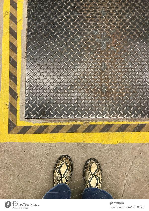 Mustermix. Schlangenlederschuhe vor gestreifter Bodenmarkierung und Schachtabdeckung streifen Abdeckung schacht schutz eisendeckel beton gelb schlangenmuster