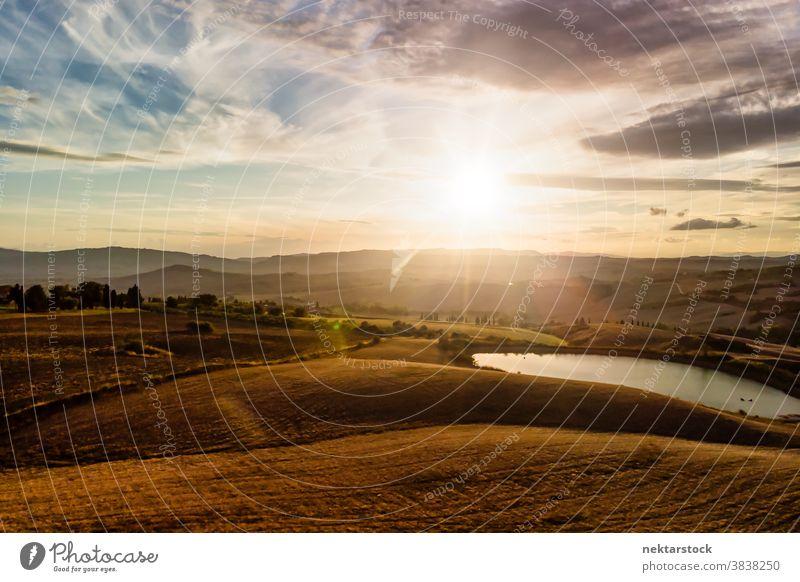 Italienisches Landschaftspanorama mit Bergsilhouetten und Wolken Toskana Wolkenlandschaft Panorama Ackerbau Feld See Sonne Sonnenaufgang ländlich Ackerland